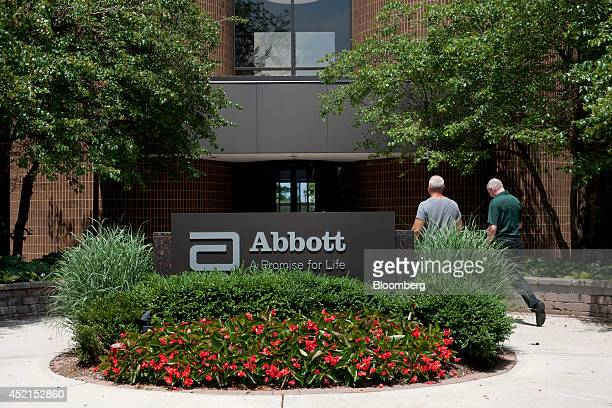 Employees walk near an Abbott Laboratories sign at the company's headquarters complex in Abbott Park, Illinois, U.S., on Monday, July 14, 2014....