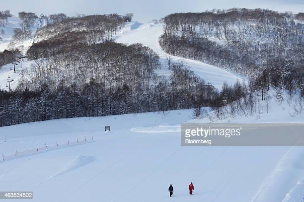 Employees walk on a slope ahead of the day's operation at the Niseko Hanazono resort operated by Nihon Harmony Resorts KK in Kutchan Hokkaido Japan...