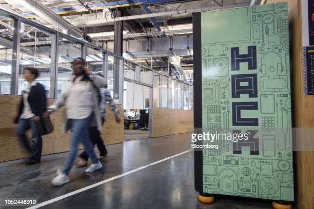 Employees walk past a Hack sign displayed inside Facebook Inc headquarters in Menlo Park California US on Wednesday Oct 17 2018 Even if it's not a...
