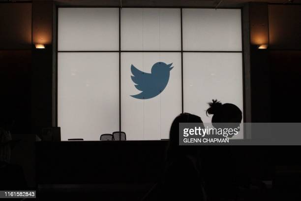 Employees walk past a lighted Twitter log as they leave the company's headquarters in San Francisco on August 13 2019 Twitter on August 13 said that...