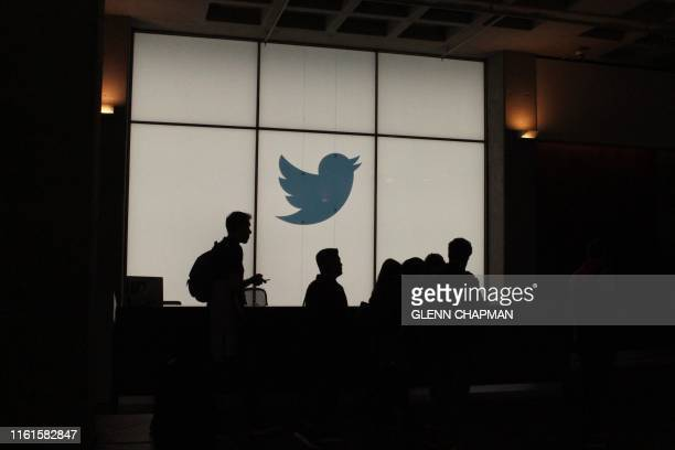 Employees walk past a lighted Twitter log as they leave the company's headquarters in San Francisco on August 13, 2019. - Twitter on August 13 said...