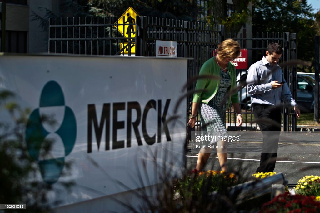 Employees walk past a Merck sign in front of the company's building on October 2, 2013 in Summit, New Jersey. The pharmaceutical company Merck & Co. announced today that it would cut 8,500 jobs and consolidate its real estate in Kenilworth, New Jersey instead of moving its headquarters to Summit as previously planned.