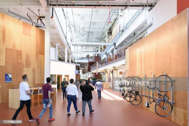 Employees walk past a wall bike rack at the new Facebook Inc. Frank Gehry-designed MPK 21 office building in Menlo Park, California, U.S., on...