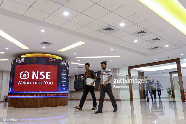 Employees walk past an electronic board displaying stock figures at the National Stock Exchange of India Ltd building in Mumbai India on Friday Dec...