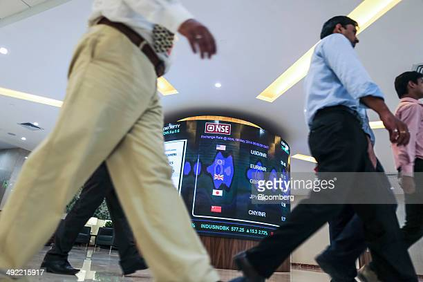 Employees walk past an electronic board displaying the rupee's exchange rates against the US dollar from top euro pound sterling Japanese yen and...