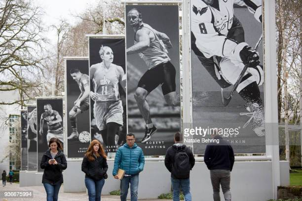 Employees walk past banners depicting athletes at Nike headquarters on March 22 2018 in Beaverton Oregon Nike the world's largest sports brand...