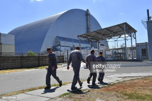 Employees walk past Chernobyl's New 108 metres Safe Confinement covering the 4th block of Chernobyl Nuclear power plant on June 8 2018 The restricted...