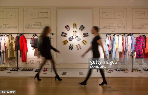 Employees walk past clothes and leather ballet pumps displayed during a preview of Audrey Hepburn's personal collection at Christie's auction house...