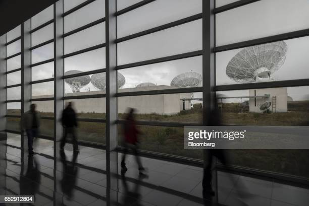 Employees walk past satellite antennas at the Bolivian Space Agency Amachuma Ground Station stands in Achocalla La Paz Department Bolivia on...