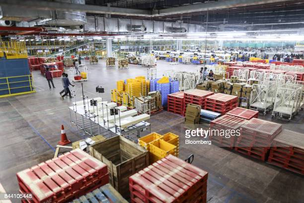 Employees walk past stacked palettes in the warehouse at the Amazoncom Inc fulfillment center in Hyderabad India on Thursday Sept 7 2017 Amazon...