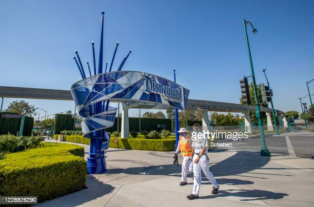 Employees walk past the entrance to Disneyland Park on Wednesday, Sept. 30, 2020 in Anaheim, CA. After suffering losses for months due to Gov....