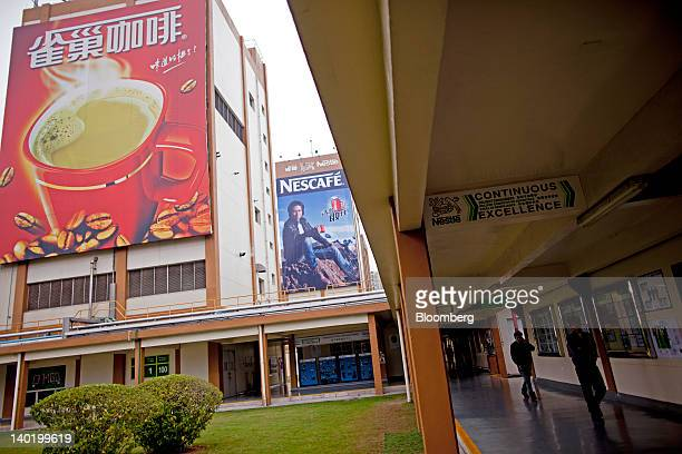 Employees walk through Nestle SA's Nescafe production facility in Dongguan Guangdong Province China on Tuesday Feb 28 2012 Nestle the world's biggest...