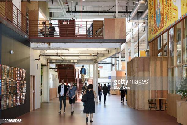 Employees walk through the main corridor at the new Facebook Inc. Frank Gehry-designed MPK 21 office building in Menlo Park, California, U.S., on...
