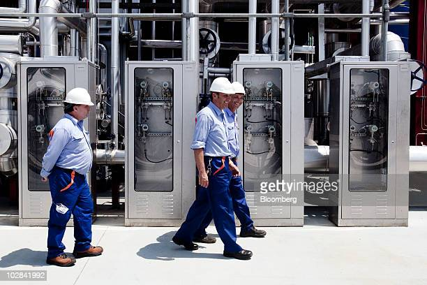 Employees walk through the world's first industrialscale hydrogen plant owned by Enel SpA in Fusina near Venice Italy on Monday July 12 2010 Enel...
