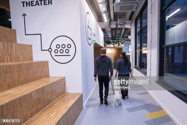 Employees walk with a dog towards a coffee area as Robert Bosch GmbH opens an Internet of Things campus in Berlin Germany on Thursday Jan 18 2018...