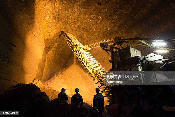 Employees watch as potash falls from a hole in the rock wall into a storage area inside the potash mine operated by OAO Uralkali in Berezniki Russia...