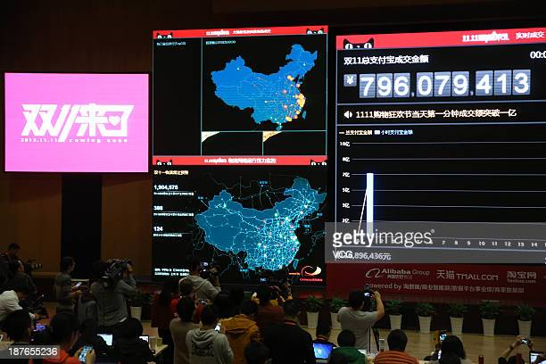 Employees watch the live broadcast of transactions during its 'Singles' Day' shopping promotion at Alibaba Headquarters on November 11 2013 in...