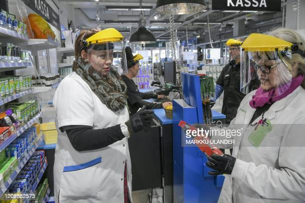 Employees wear protective clothing against the novel coronavirus at the Asema Apteekki pharmacy in Vantaa Finland on April 1 2020 / Finland OUT