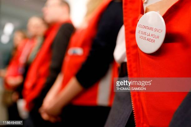 SNCF employees wearing a badge reading SNCF volunteer I'm here to help stand inside the Montparnasse train station in Paris on December 4 on the eve...