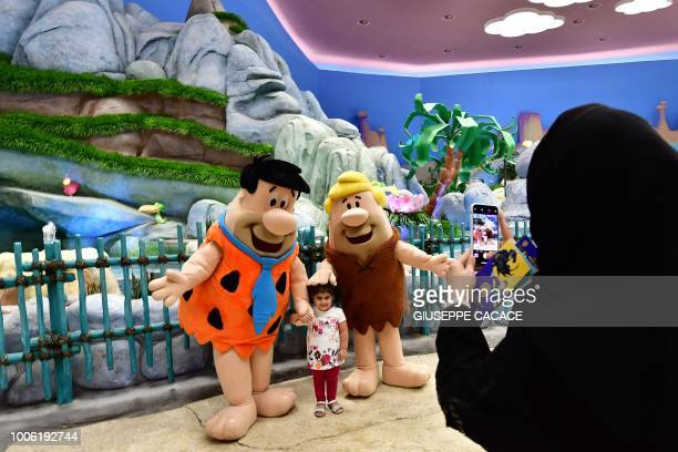 Employees wearing a Fred Flintstone and Barney Rubble costume pose for a picture with a girl at Warner Bros World the firstever Warner branded indoor...