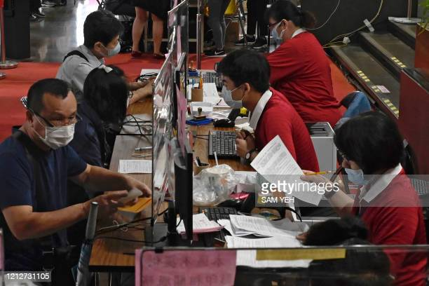 Employees wearing face masks due the COVID-19 pandemic sit behind plastic partitions as they check tax documents submitted by local residents at the...