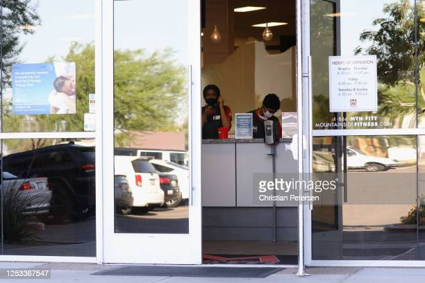Employees wearing face masks work behind the counter at Mountainside Fitness on June 29 2020 in Glendale Arizona Arizona Gov Doug Ducey ordered all...
