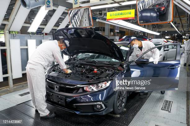 Employees wearing face masks work on a production line at an auto plant of Dongfeng Honda Automobile Co. Ltd. On March 23, 2020 in Wuhan, Hubei...