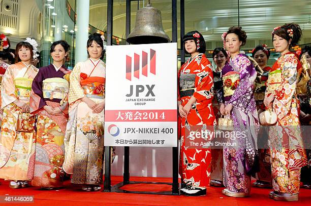 Employees wearing kimono pose for photos after the opening ceremony of the first trading day of the year at Tokyo Stock Exchange on January 6 2014 in...
