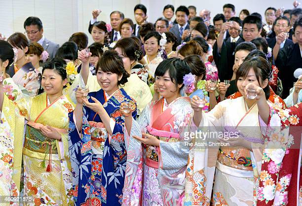 Employees wearing kimono toast glasses during a opening ceremony of the first trading day of the year at Fukuoka Stock Exchange on January 6 2014 in...