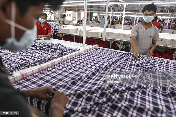 Employees wearing masks handle fabric on the cutting division production line at the CBC Fashions Pvt factory in Tiruppur Tamil Nadu India on...
