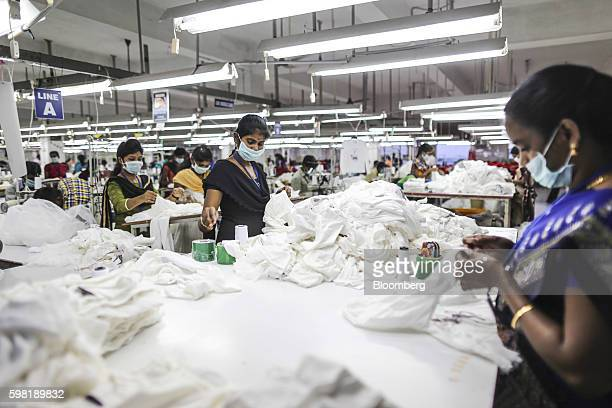Employees wearing masks handle garments on a production line at the CBC Fashions Pvt factory in Tiruppur Tamil Nadu India on Thursday Aug 4 2016...