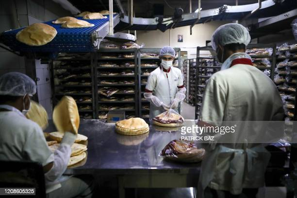 Employees wearing personal protective equipment pack bread at a bakery in the Lebanese capital Beirut on March 30 2020 Lebanon has reported 446...