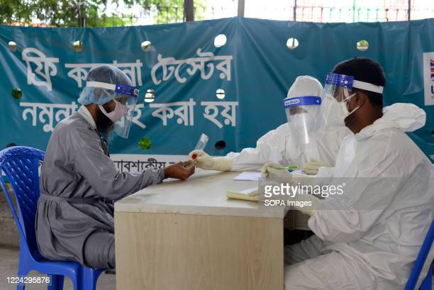 Employees wearing personal protective equipment suit talk to a man, who has come to get tested for the COVID-19. Mugda Medical College and Hospital...