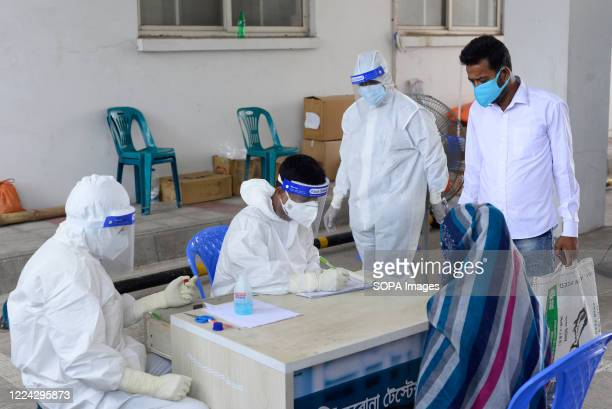 Employees wearing personal protective equipment suits talk with a woman, who has come to get tested for the Covid-19. Mugda Medical College and...