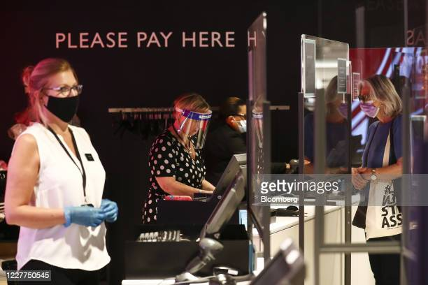 Employees wearing protective face masks and facial visors serve customers from behind a perspex screen at the check out area inside a John Lewis...