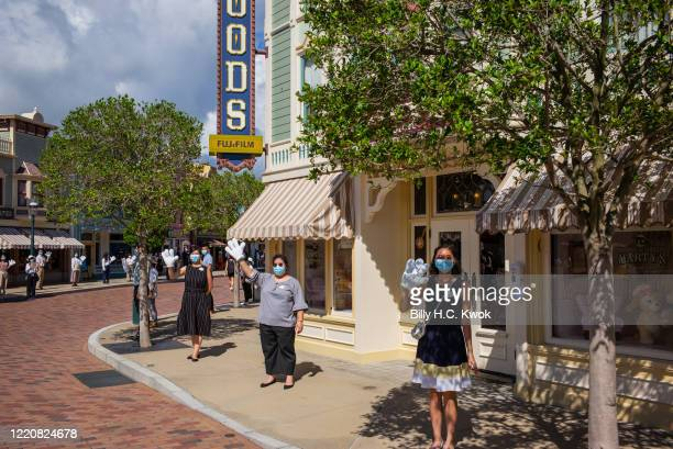 Employees wearing protective face masks and Mickey Mouse hands welcome visitors at Walt Disney Co's Disneyland Resort on June 18 2020 in Hong Kong...