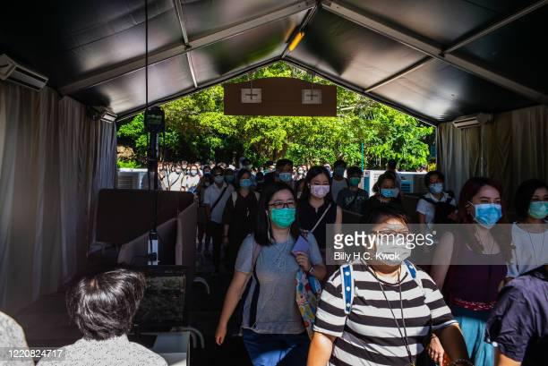 Employees wearing protective face masks walk towards Walt Disney Co's Disneyland Resort on June 18 2020 in Hong Kong China