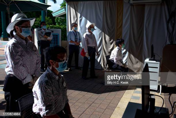 Employees wearing protective face masks work at a temperature screening point at the entrance to Walt Disney Co's Disneyland Resort on June 18 2020...