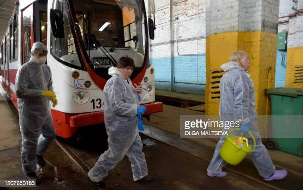 Employees wearing protective gear disinfect a tram as part of preventive measures against the COVID19 coronavirus in Saint Petersburg on March 19 2020
