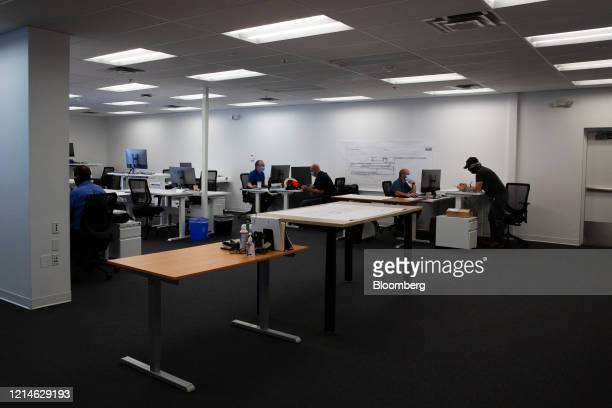 Employees wearing protective masks sit a work stations at a Lucid Motors Inc. Facility in Casa Grande, Arizona, U.S., on Thursday, May 14, 2020....