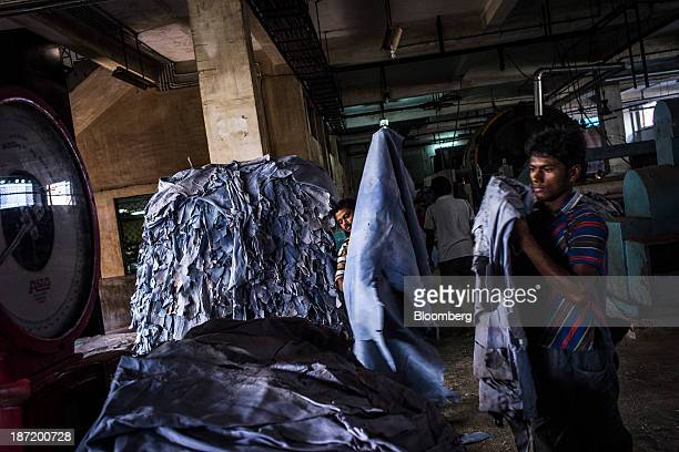 Employees weigh a stack of tanned leather skins at the New Horizons Ltd tannery in the Bantala area of Kolkata West Bengal India on Wednesday Oct 30...