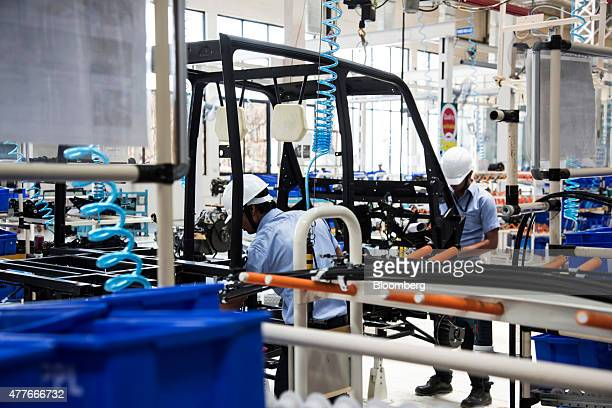 Employees wire the frame of an Eicher Polaris Pvt Multix personal utility vehicle at the company's factory in Jaipur Rajasthan India on Thursday June...