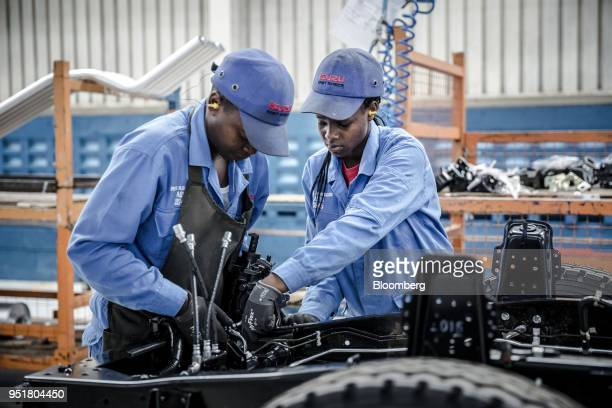 Employees work affixing electronics to the chassis of an Isuzu truck on the assembly line inside the Isuzu East Africa Ltd plant in Nairobi Kenya on...