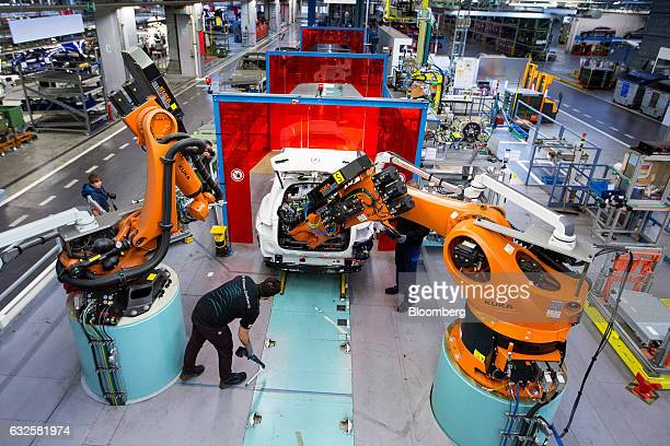 Employees work alongside robotic arms manufactured by Kuka AG as a battery pack is installed in a MercedesBenz GLC hybrid automobile on the assembly...