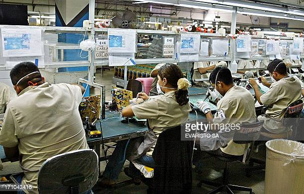 Employees work at a computers assembly line 17 September 2004 at Manaus Duty Free Zone in the Amazon north Brazil The ZFM is one of the main...