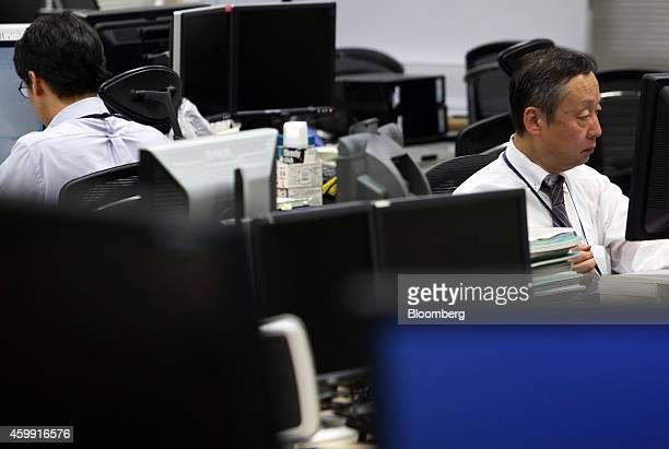 Employees work at a foreign exchange brokerage in Tokyo Japan on Thursday Dec 4 2014 Japanese stocks rose for a fifth day with the Topix index...