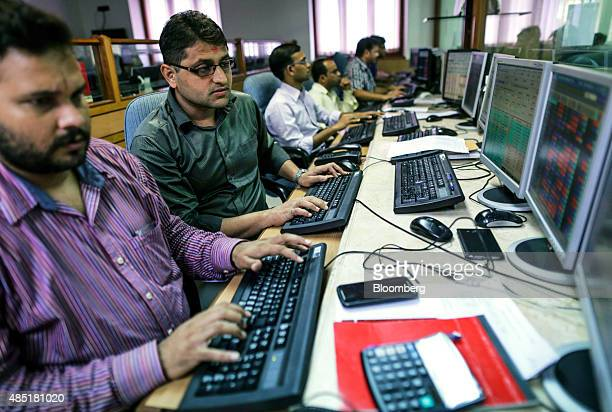 Employees work at computers at a brokerage firm in Mumbai India on Tuesday Aug 25 2015 Indian stocks advanced in volatile trading a day after the...