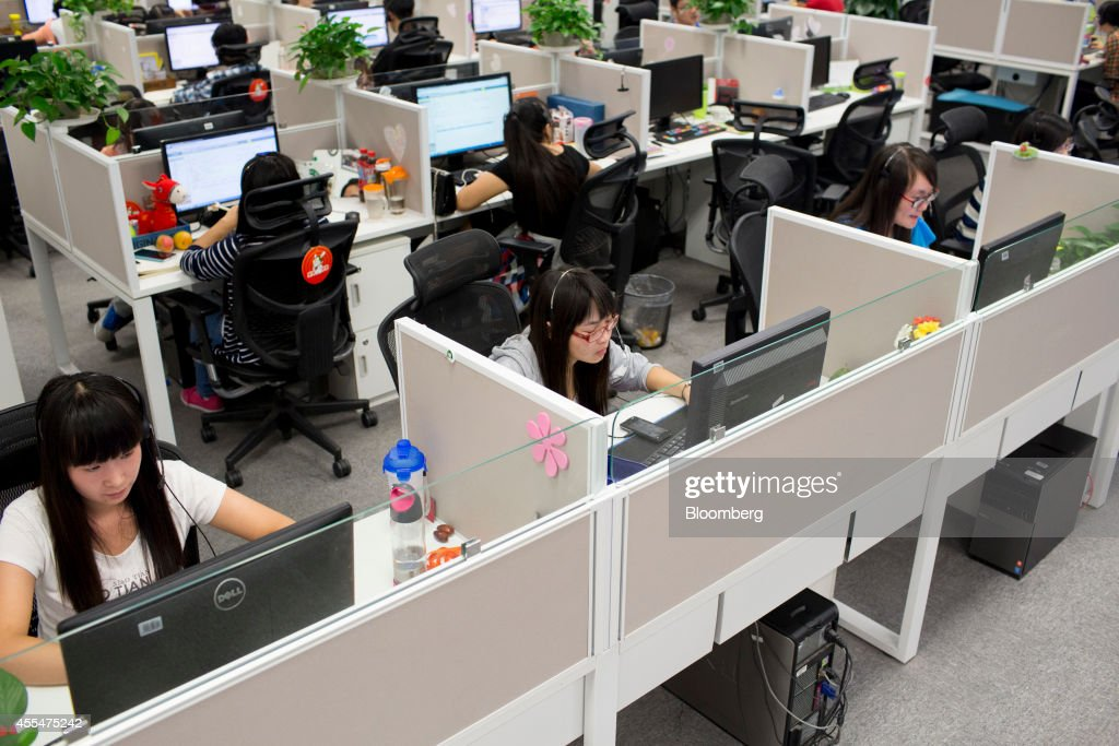 Employees work at computers in the customer support call center at a Xiaomi Corp. office in Beijing, China, on Friday, Sept. 12, 2014. Xiaomi Chief Executive Officer Lei Jun plans to boost global smartphone sales fivefold to 100 million units next year. Photographer: Brent Lewin/Bloomberg via Getty Images