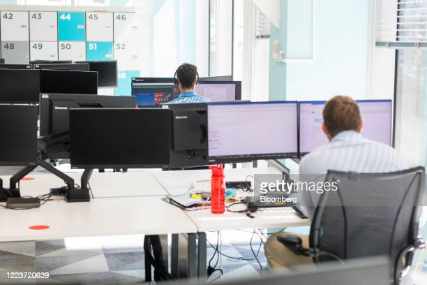 Employees work at desks at a social distance at Cushman & Wakefield Plc's offices during the first phase of the reoccupation of their headquarters in...