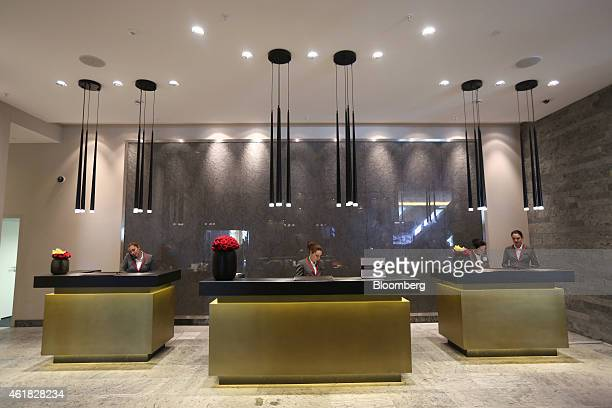 Employees work at reception desks in the lobby of the InterContinental Hotel Davos operated by InterContinental Hotels Group Plc ahead of the World...